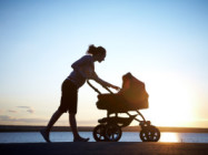 Silhouette of young mother with a stroller