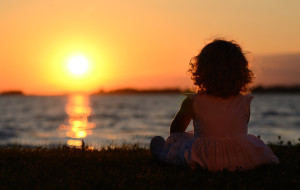 Relaxing young child in sunset