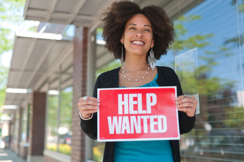 lady holding help wanted sign
