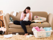mother holding baby on couch with laundry everywhere