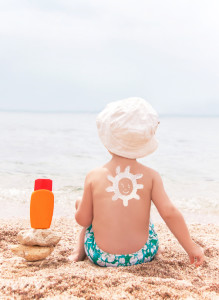 The sun drawing sunscreen on baby (boy)  back.