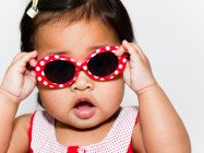 baby girl with red and white polka dotted sunglasses