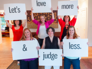"people holding a sign saying ""let's love more and judge less."""