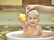 smiling baby getting a bath holding a rubber ducky