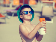small boy in green hat spraying on sunscreen