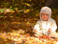 Baby smiling and sitting in autumn leaves.