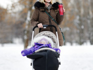 Young mother walking with baby stroller in winter