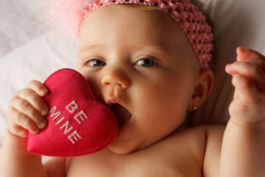 Valentine's day picture of baby chewing on a heart that says Be Mine on white fabric surface