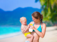 Young mother and cute baby boy enjoying summer vacation in a tropical resort, parent applying sun screen using lotion spray for safe tan and skin care