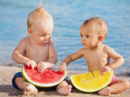 After sea swimming asian and caucasian babies have a fun and eat fresh fruits on sand beach. Healthy kids food, active lifestyle, water activity and children travel with parents on family vacation.