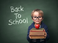 Young child holding stack of books and back to school written on chalk blackboard