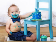 One year old boy enjoys his birthday cake on his first birthday.