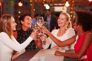 Girlfriends at rooftop party, holding up glasses of wine