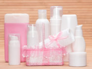 Collection of cosmetic products for skincare with a charming wicker basket and towel on a bamboo mat. White and pink colors