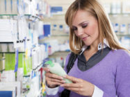 Portrait of blonde woman reading label of shampoo in pharmacy.