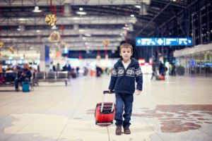 Cute little boy, traveling home for the holidays, Christmas time, waiting happily for the plane to departure