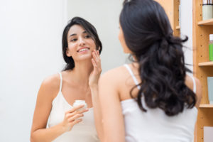Woman caring of her beautiful skin on the face standing near mirror in the bathroom. Beautiful young woman applying moisturizer on her face. Smiling girl holding little jar of skin cream and applying lotion on face.