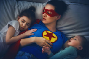 protection of the mother superhero; Adorable little children girls are napping in the bed with their mom. Quiet sleep under the protection of the mother superhero.
