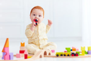 cute ginger baby playing with toy railway road at home. Tasting wagon