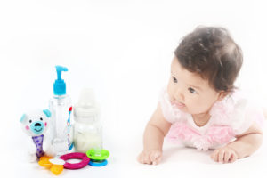 Infant baby girl crawling next to essential baby items such as hand sanitizers for baby, toys, baby bottle, breast milk, teething ring and pacifier. Isolated on white background and with copyspace.
