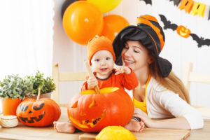 mother and baby cut a pumpkin for Halloween in the kitchen at home