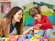 Mother and daughter playing together with colorful construction toys on a carpet on the floor af a bedroom at home