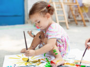 Cute little caucasian Girl enjoying Painting at the backyard with paper, water colour and art brush. Selective focus.