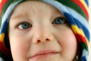 A toddler wearing a striped hat looks sad. Shallow DOF; focus on face.VIEW THE ENTIRE