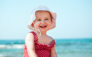 Cute 18-month old toddler having fun on beach