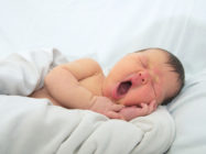 funny baby face,newborn with jaundice on white blanket, infant healthcare concept
