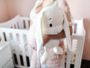Close up of pregnant woman holding bunny toy while standing in baby room.
