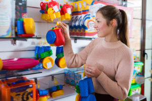 Modern female in the children's store assortment of plastic toys