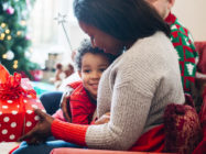 A little boy happily hugs his mother as she receives a gift from him on Christmas morning.
